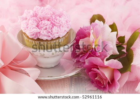 A pretty pink cupcake in a teacup surrounded by pink boa, bow, and pink roses, horizontal with copy space
