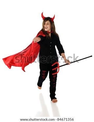 A pretty preteen girl running and pointing forward in a devil costume.  Isolated on white.