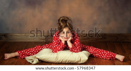 A pretty preteen with her pillow doing splits in polka-dot pajamas.