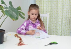 A pretty schoolgirl sits at a table and embroiders, does needlework, sews.Hobby concept, needlework.