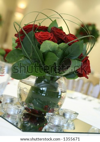 stock photo A pretty table centerpiece made out of red roses and bear