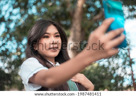 A pretty vain young asian woman in a student uniform takes a selfie of herself while at the park. Taking a photo for social media. Stock photo ©