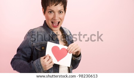 A pretty woman against pink hold her valentine's card with a heart on it