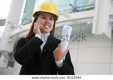 A pretty woman architect holding blueprints on the phone