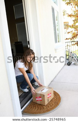 A pretty woman at home picking up delivery box package - stock photo