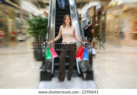 A pretty woman coming down the escalator with shopping bags in hand