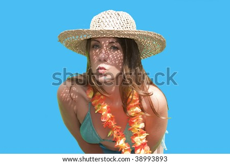 A pretty woman/girl in straw hat posing by blowing a kiss for the camera on a Hawaiian vacation.