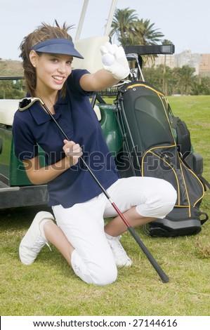 A pretty woman golfer holding a golf ball