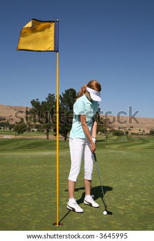 A pretty woman golfer putting for par on the gold course