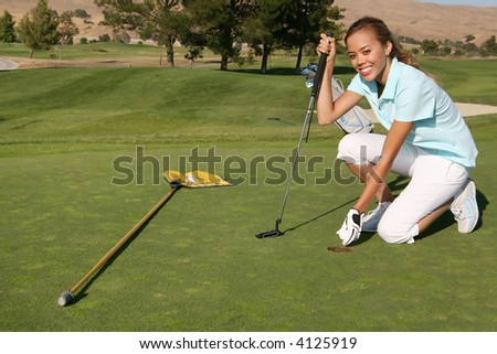 A pretty woman golfer retrieving her ball from the hole
