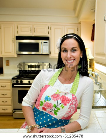 A pretty woman in a clean, modern, kitchen, leaning on the counter and smiling.