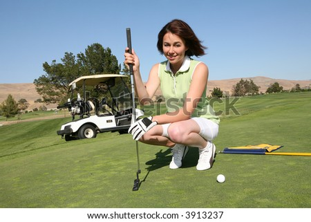 A pretty woman in the middle of a golf game