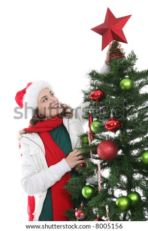 A pretty woman putting a star on the Christmas tree - stock photo