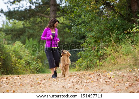 A pretty woman walking her dog