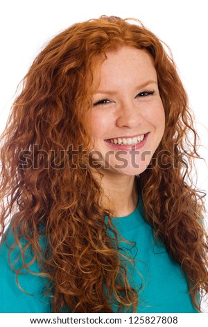 A pretty woman with naturally curly red hair and a happy, vibrant smile.