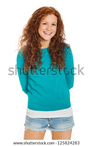 A pretty woman with red hair and freckles wearing short denim shorts.