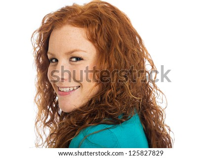 A pretty woman with red hair looking back over her shoulder.