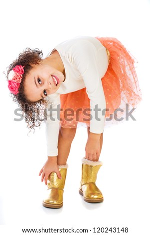 A pretty young African American girl putting on her gold boots.