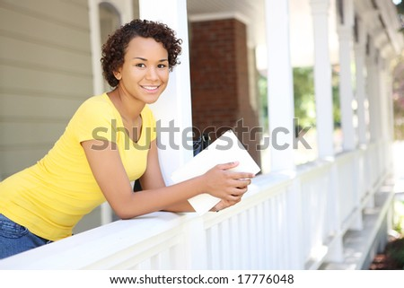 A pretty, young african woman on porch reading a book