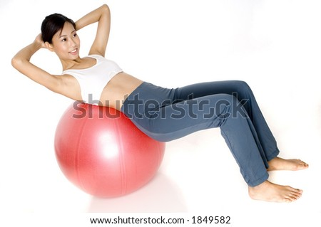 A pretty young asian woman exercises on a fitness ball