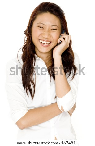 A pretty young asian woman laughs as she talks on a cellphone