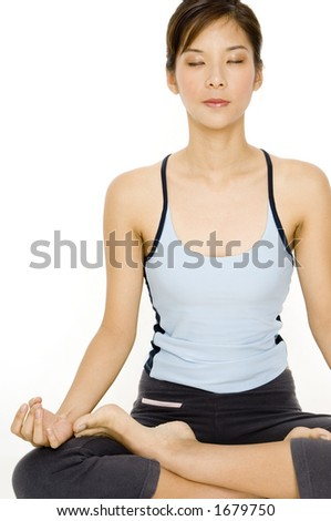 A pretty young asian woman meditating in a sitting yoga position