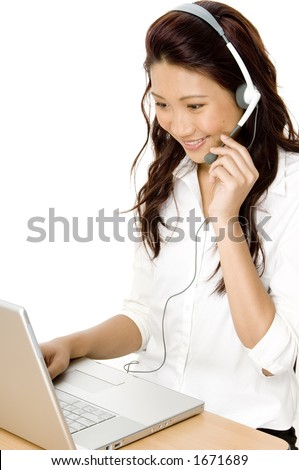 A pretty young asian woman working on a helpdesk