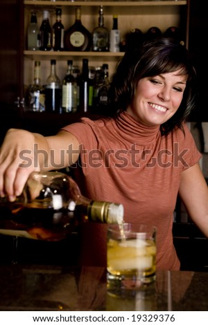 A pretty young bartender pouring a cold drink