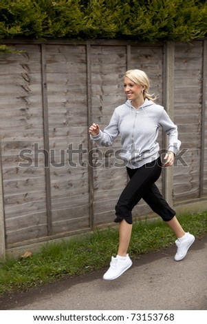 a pretty young girl outside running along a path