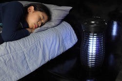 a pretty young girl sleeping near the insects mosquito electric killer blue light lamp is put on wooden bed table in the dark bedroom for better sleeping ambient safty condition at night from insects
