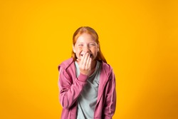 A pretty young red haired teenager covers her mouth with her hand while nervously laughing. Cute preteen Caucasian girl giggles with her hand close to her lips. Concept of fun, pranks, joking around