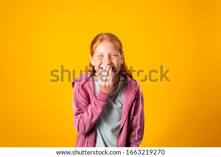 A pretty young red haired teenager covers her mouth with her hand while nervously laughing. Cute preteen Caucasian girl giggles with her hand close to her lips. Concept of fun, pranks, joking around ストックフォト ©