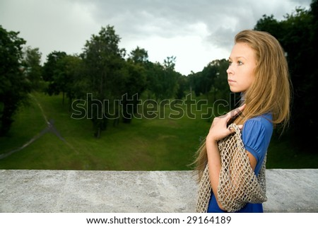 A pretty young woman in a blue dress outdoors - stock photo