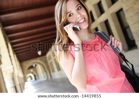 A pretty, young woman on the college campus talking on phone