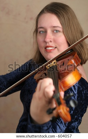 A pretty young woman playing classical violin.