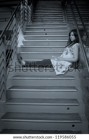 A pretty young woman sitting on stairs feeling sad.
