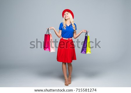 A pretty young woman stylishly dressed in a hat with bags after shopping in the mall isolated #715581274