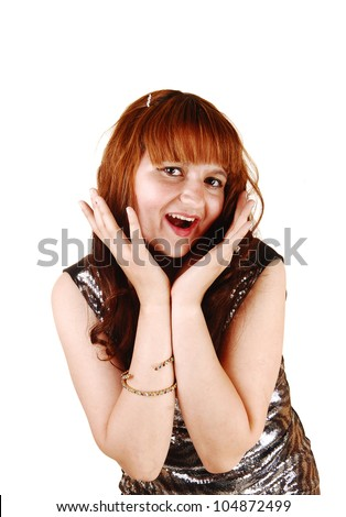 A pretty young woman with long red hair posing in a portrait shot for white background, with both hands on her face and laughing. - stock photo