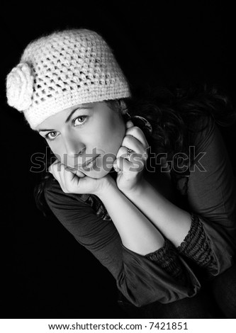 A pretty, young woman with retro hat, on black background