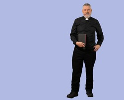 A priest in a black shirt with a white clerical collar. The older man has gray hair, a beard and a Bible in his hand. The person is isolated against a blue background.