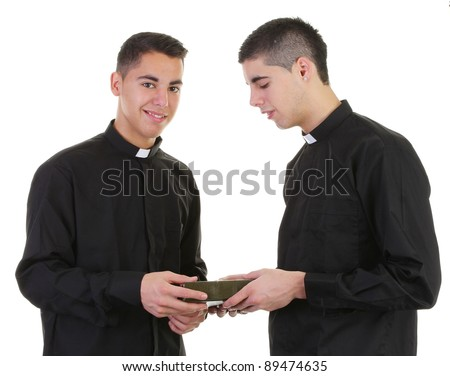 A priest passing a bible to another priest