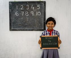 A Primary School Girl holding a Green Board written