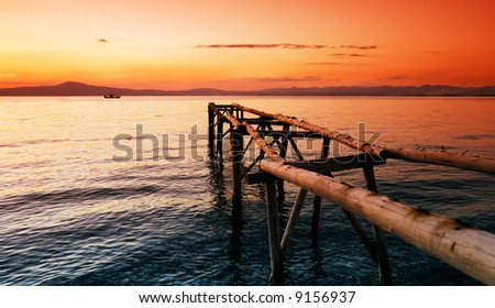 A primitive wooden pier, photographed during a glorious sunset,  extends into the sea and leads the eye to a fishing boat in the distance.