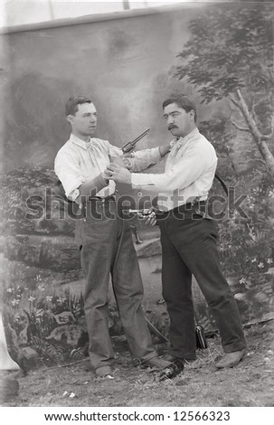 A print from a glass negative taken in an an old view camera about 1890. Two men pointing guns at each other.