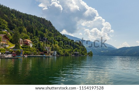 A pristine Austrian landscape, with majestic Alpine mountains, crystal clear waters of a lake and complex clouds rolling over the sky