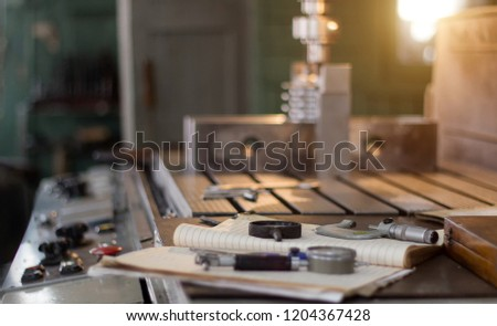A private workshop for working with metal parts, in the background a drilling machine drills a hole in the pulley, on the table lie measuring instruments