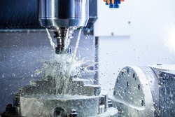 a process of industrial wet milling in 5-axis cnc machine with coolant flow under pressure and freezed splashes