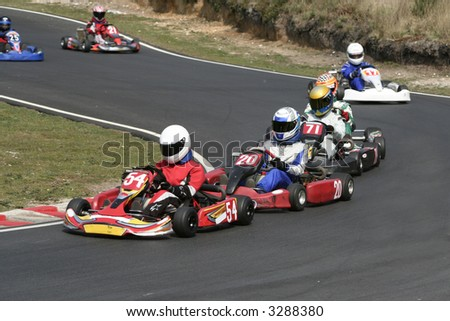 A procession of go karts racing around a bend