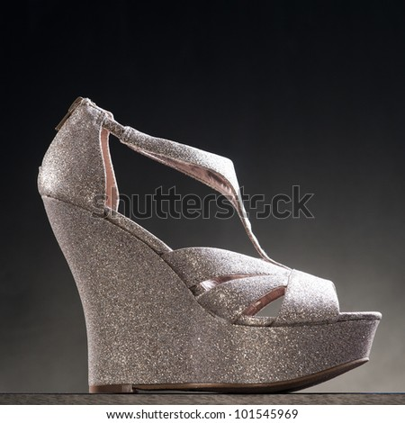 A product shot of high heel shoe against a dark coloured background