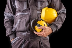 A production worker in workwear with a helmet and hearing protectors in hand. Special workwear for employees. Dark background.